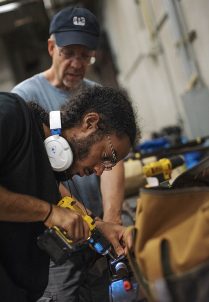 Broadway Camp production students use a drill to attach straps to prop guns for Les Miserables at Proctors Thursday, July 15, 2019.